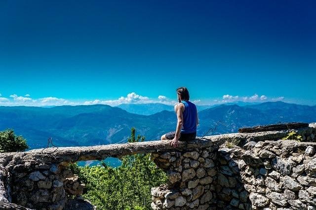 אדם יושב על קיר אבנים - אלבניה